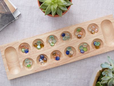 A standard mancala board: twelve holes, two pits, and four pieces in each hole.