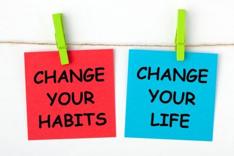 Change Your Life by Changing Your Habits text written on color notes with wooden pinch.